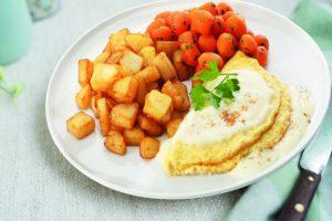 Bord met Omelet met kaassaus en worteltjes